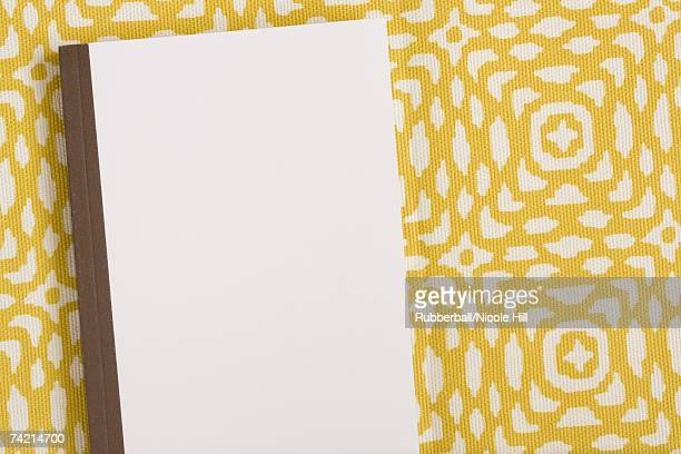 Closed hardcover notebook with yellow and white background pattern