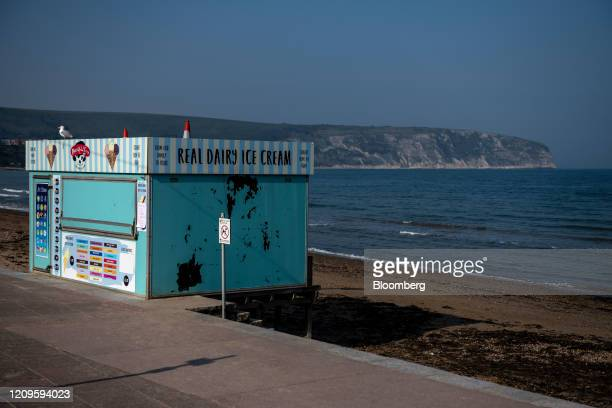 A closed ice cream vendor stand closed beside a deserted beach during the national lockdown on Easter weekend in Swanage UK on Friday April 10 2020...