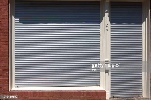 closed jalousie window - closed shop - fensterladen stock-fotos und bilder