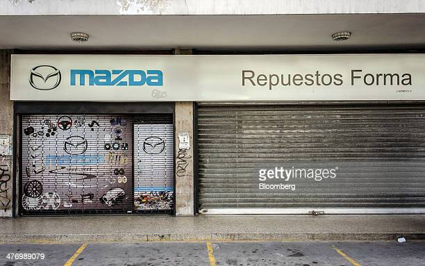 A closed Mazda Motor Corp parts and accessories dealership is shuttered with a metal gate in the Altamira section of Caracas Venezuela on Friday Feb...