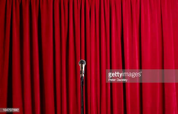 closed red curtains with microphone - マイクスタンド ストックフォトと画像