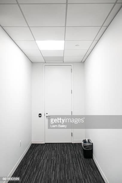 Closed secure white door with bin otside