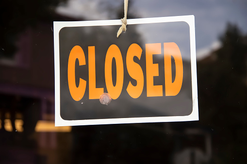 Closed sign hanging in business window by a string - crooked with glob of glue also attaching it to window - some abstract reflections 1049104302