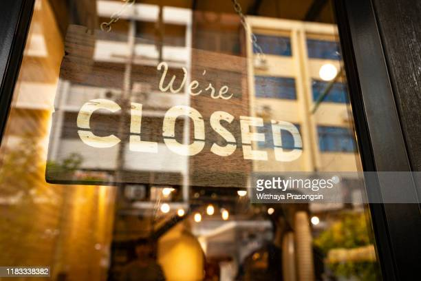 closed sign hanging in business window by a string - crooked with glob of glue also attaching it to window - sluiten stockfoto's en -beelden