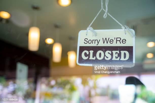 closed sign hanging on glass door in small business window - opening event stockfoto's en -beelden