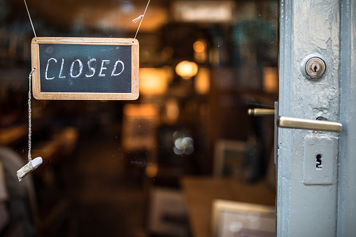 Closed - sign hanging on glass door 1213585784