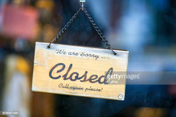 closed sign hanging on glass door - cartello chiuso foto e immagini stock