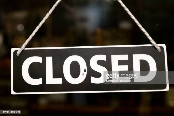 Closed sign hangs in the window of small business on December 11, 2020 in Cardiff, Wales. Many UK businesses are announcing job losses due to the...