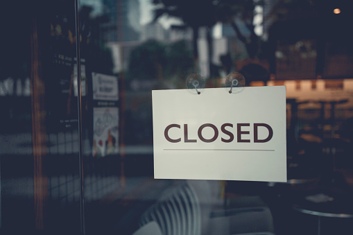 Closed sign on a glass door 1008426566