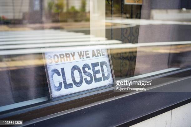 closed sign seen through a store window - falência imagens e fotografias de stock