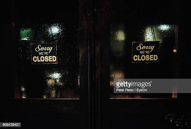 Closed Signs On Wet Glass Door Of Store At Night