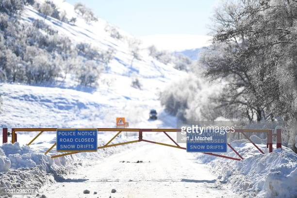 Closed snow gates are seen on a road, with a sign reading 'Police notice road closed snow drifts' on February 11, 2021 in Braemar, Scotland. A low of...