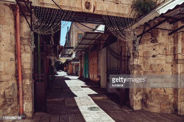 closed stores and empty alley in jerusalem old city bazaar - jerusalem stock pictures, royalty-free photos & images