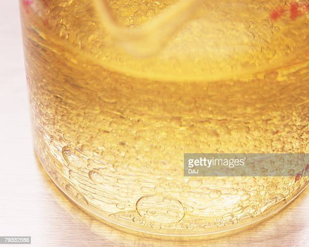 Closed Up Image of Some Beige-colored Oil in a Glass Beaker, Containing a Lot of Bubbler, High Angle View