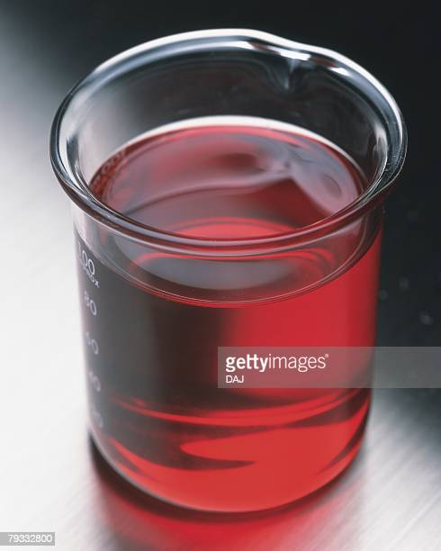 Closed Up Image of Some Red Oil in a Beaker, Standing on a Silvern Surface, High Angle View