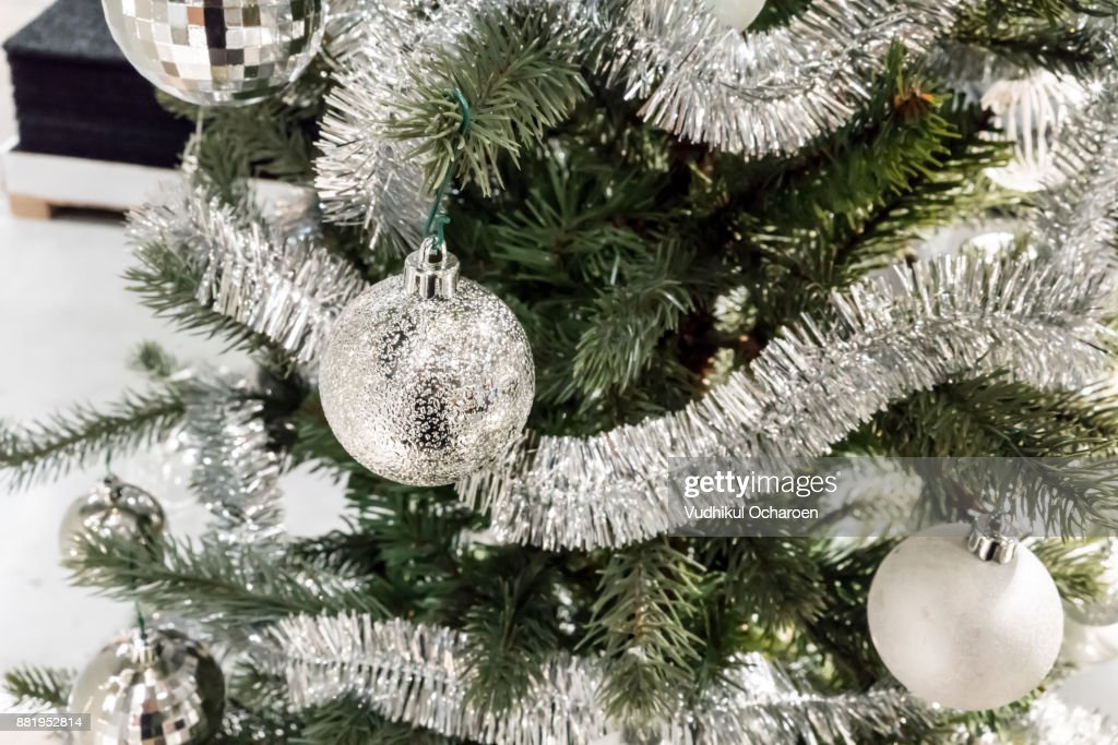 Closed up shiny silver ball on decorative christmas tree with
