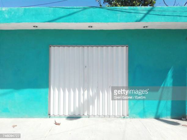 Closed White Metallic Gate On Turquoise Wall