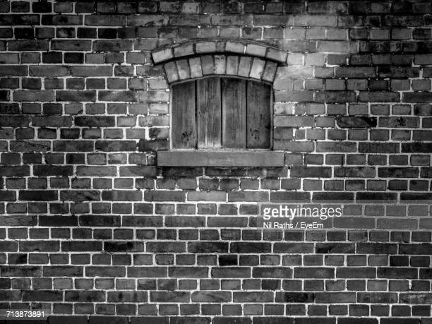 Closed Window Amidst Brick Wall