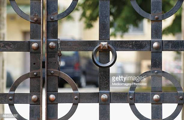 Closed wrought iron gate with a house behind it