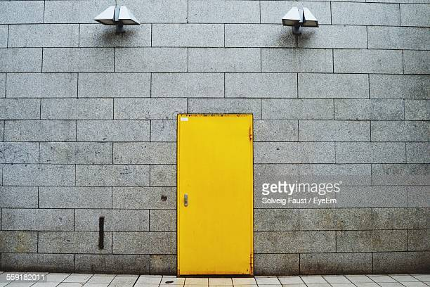 closed yellow door of building with electric lights - yellow stock pictures, royalty-free photos & images