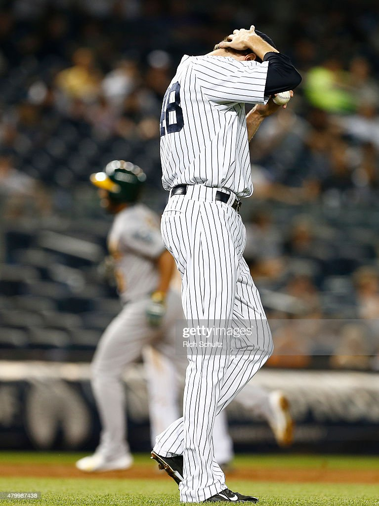 Closer Andrew Miller #48 of the New York Yankees lowers his head after giving up a two run home run to Marcus Semien #10 of the Oakland Athletics 5-4 during the ninth inning a MLB baseball game at Yankee Stadium on July 8, 2015 in the Bronx borough of New York City. The Yankees defeated the A's 5-4.