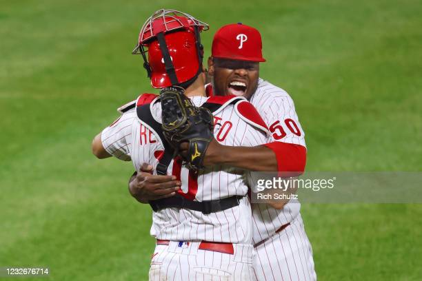 Closer Héctor Neris of the Philadelphia Phillies hugs catcher J.T. Realmuto after striking out Lorenzo Cain of the Milwaukee Brewers with the bases...