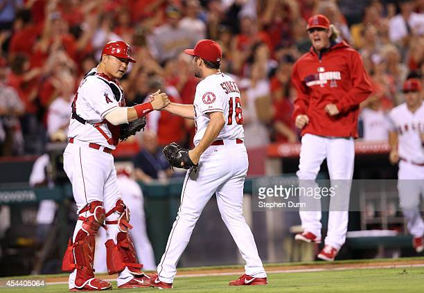 Closer Huston Street and catcher Hank Conger of the Los Angeles Angels of Anaheim shake hands as pitcher Jered Weaver celebrates in the background...