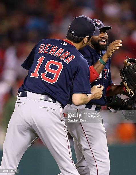 Closer Koji Uehara of the Boston Red Sox greets center center fielder Jackie Bradley Jr #25 after getting the final out of the ninth inning and...