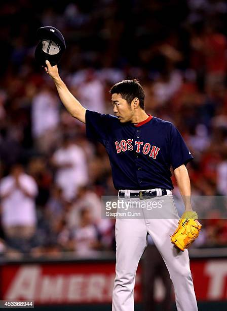 Closer Koji Uehara of the Boston Red Sox tips his cap center center fielder Jackie Bradley Jr #25 after Bradly made a leaping catch on a deep drive...