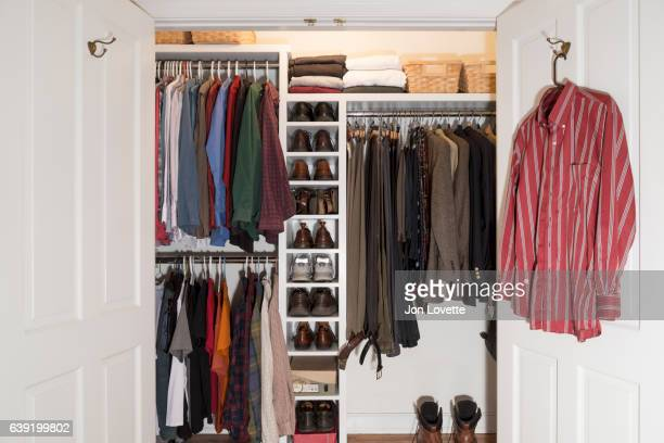 closet in home with mens clothes arranged neat - walk in closet stock photos and pictures