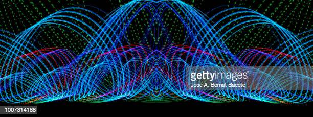 close-up abstract pattern of intertwined colorful light beams of color blue, green and pink on a  black background. - hellblau stock-fotos und bilder