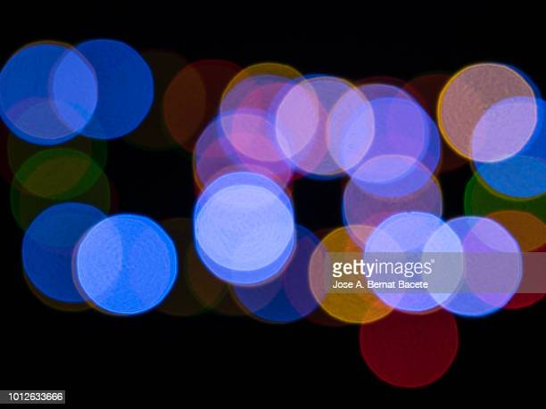 close-up abstract pattern of intertwined colorful light beams of color light blue, yellow and green on a  black background. - angel halo stock pictures, royalty-free photos & images