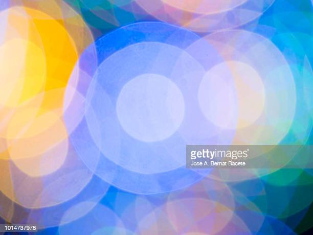 close-up abstract pattern of intertwined colorful light beams of color light blue, yellow and green on a  black background. - image focus technique stock pictures, royalty-free photos & images
