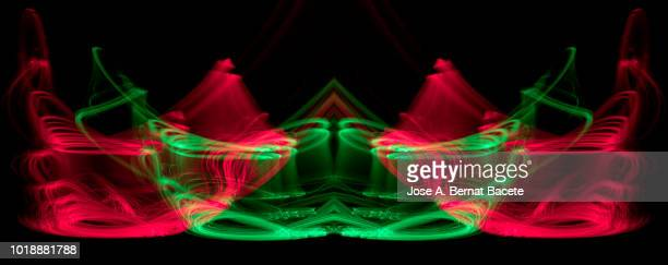 Close-up abstract pattern of intertwined colorful light beams of color red and green on a  black background.