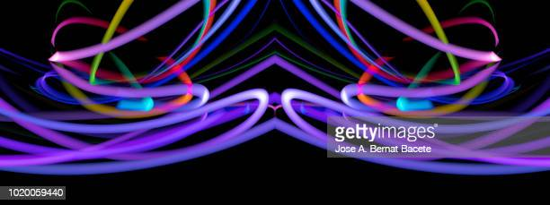 Close-up abstract pattern of intertwined colorful light beams of color light pink and violet on a  black background.