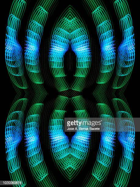 Close-up abstract pattern of intertwined colorful light beams of color light blue and green on a  black background.