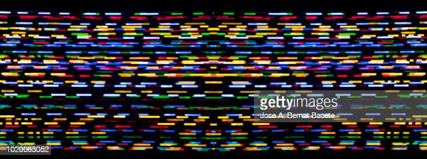 Close-up abstract pattern of intertwined colorful light beams of color light blue, red and yellow on a  black background.