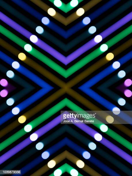 Close-up abstract pattern of intertwined colorful light beams of color violet, green and white on a  black background.