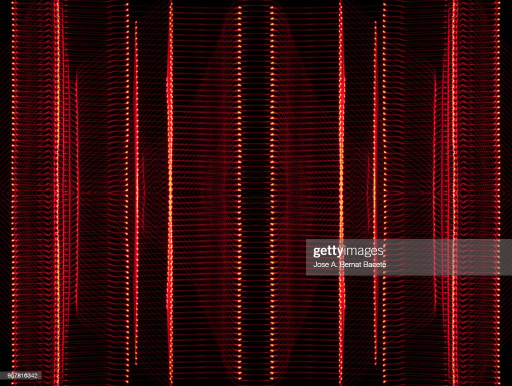 Close-up abstract pattern of intertwined colorful light beams of color red on a  black background. : Stock Photo