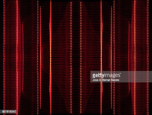 close-up abstract pattern of intertwined colorful light beams of color red on a  black background. - listrado - fotografias e filmes do acervo