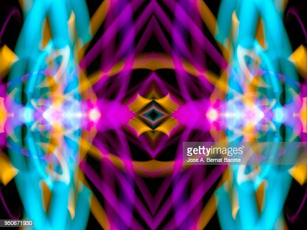 Close-up abstract pattern of intertwined colorful light beams of colors pink, green and blue on a  black background.