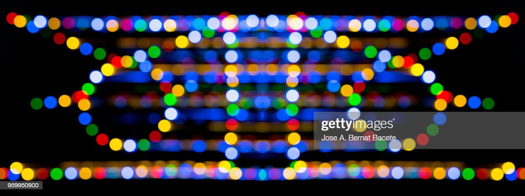 Close-up abstract pattern of intertwined colorful light beams of colors red, green and blue on a  black background. : Stock-Foto