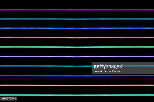 Close-up abstract pattern of intertwined colorful light beams of colors red, green and blue on a  black background.