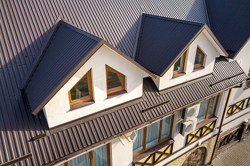 Close-up aerial view of building attic rooms exterior on metal shingle roof, stucco walls and plastic windows. 1145254175