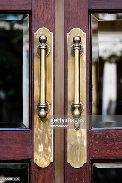 Closeup antique brass door handles on wooden door with glass