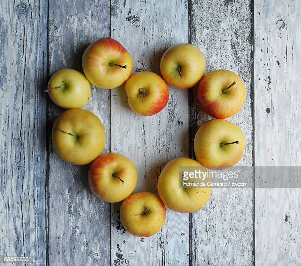 Close-Up Apples In The Shape Of A Heart Against White Wooden Table
