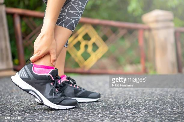close-up asian woman standing on road holds her ankle injury after jogging - sprain stock pictures, royalty-free photos & images