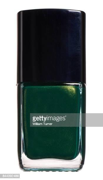 A close-up beauty image of a green nail polish bottle