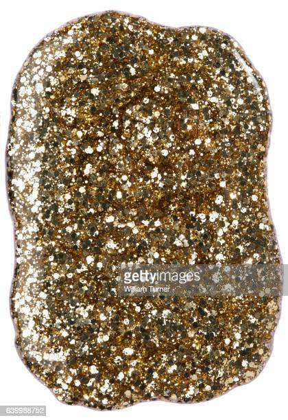 A close-up beauty image of a sample of gold glitter nail polish
