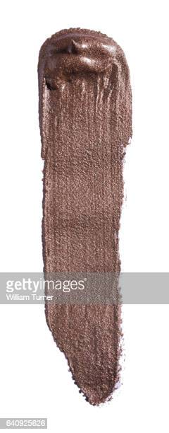 A close-up beauty image of a sample of metallic brown lip gloss